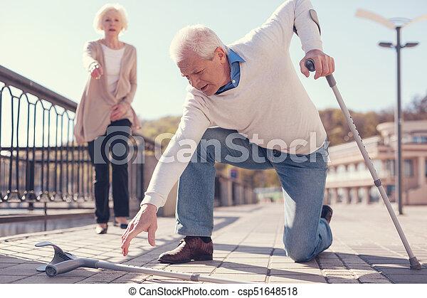 Senior man picking up his fallen crutch - csp51648518
