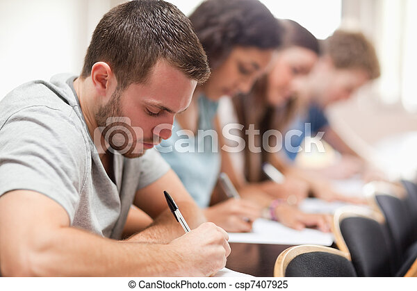 Serious students sitting for an examination - csp7407925