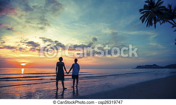 Silhouette of young couple on their honeymoon standing on Sea beach at amazing sunset. - csp26319747