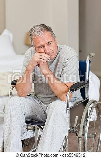 Smiling senior man in his wheelchair at home - csp5549512