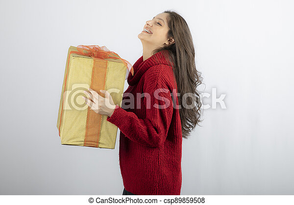 Smiling woman in red sweater holding Christmas present - csp89859508