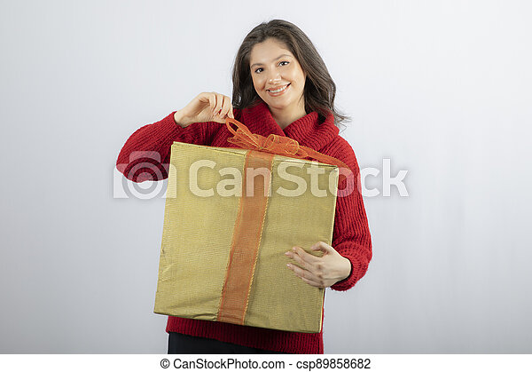Smiling woman in red sweater opening a box of Christmas present - csp89858682