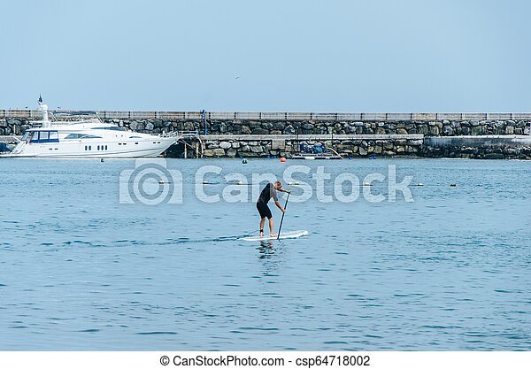Stand up paddle board man paddleboarding on Peruvian beach standing happy on paddleboard on blue water. - csp64718002
