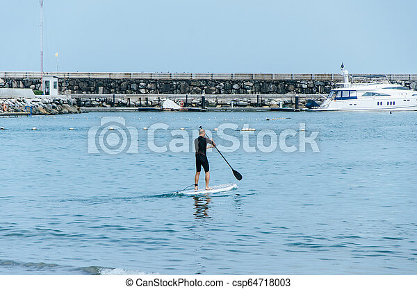 Stand up paddle board man paddleboarding on Peruvian beach standing happy on paddleboard on blue water. - csp64718003