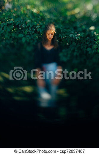 Stylish hipster woman posing at green leaves bush, atmospheric moment. Fashionable woman in denim jeans and black shirt relaxing in park. Selective focus, creative image. Space for text - csp72037487