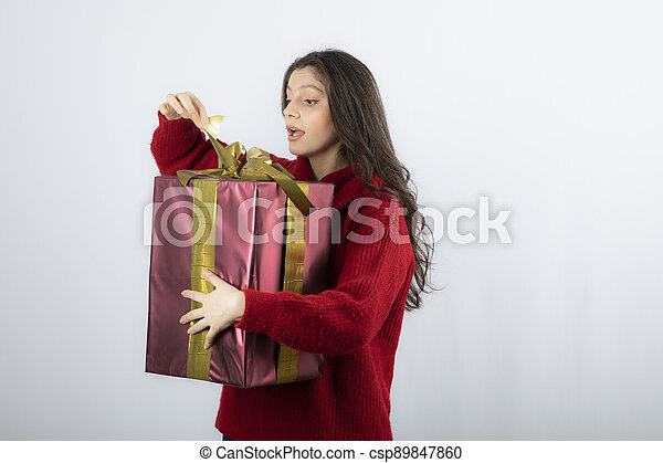 Surprised woman in red sweater opening a box of Christmas present - csp89847860