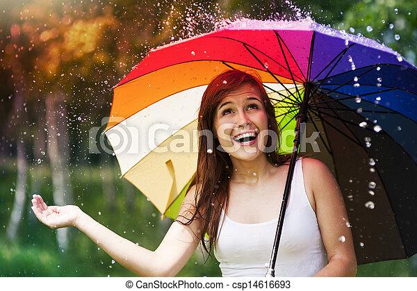 Surprised woman with umbrella during summer rain - csp14616693