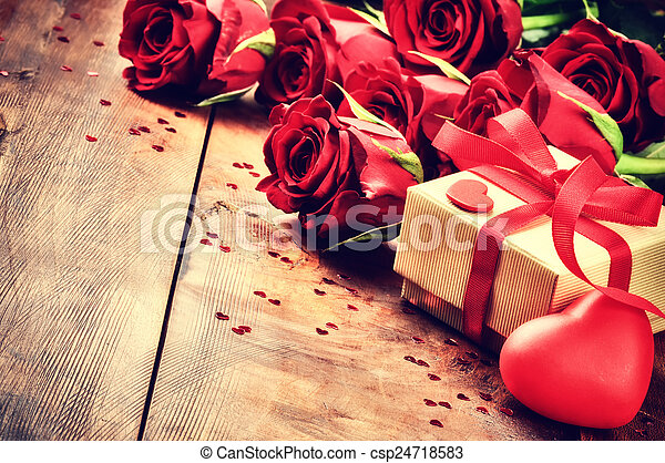 Valentine's setting with bouquet of red roses and present - csp24718583
