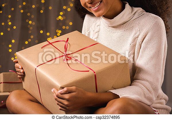 Woman holding christmas present - csp32374895