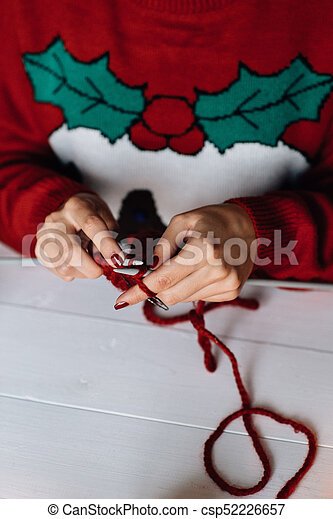Woman in red Christmas sweater knits. - csp52226657