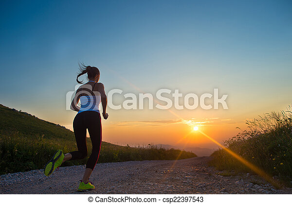 woman running on a mountain road at summer sunset - csp22397543