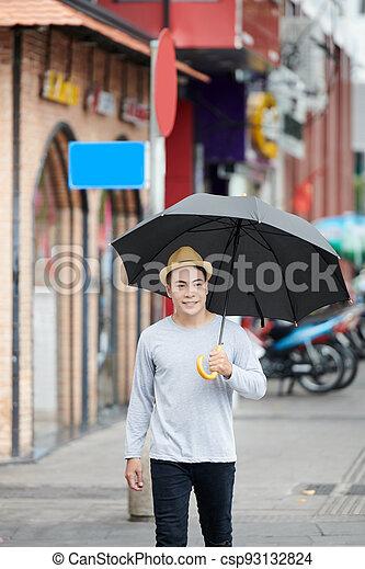 Young Asian Man Walking with Umbrella - csp93132824