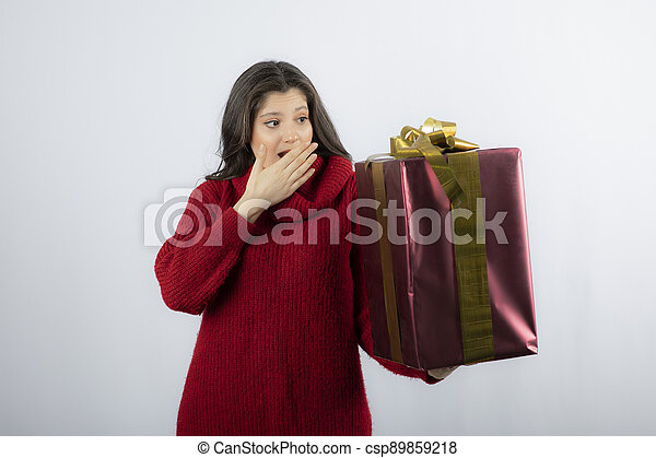 Young woman holding Christmas gift over white background - csp89859218
