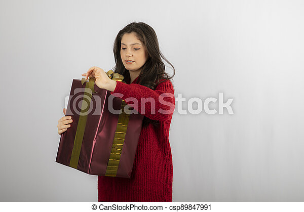 Young woman in red sweater opening a box of Christmas present - csp89847991
