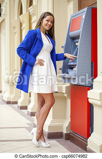 Young woman inserting a credit card to ATM - csp66074982
