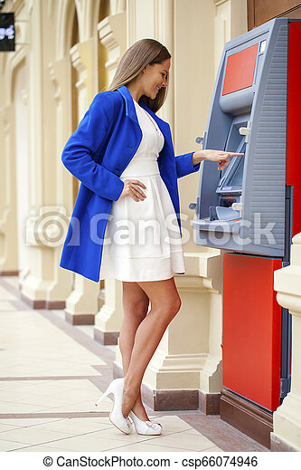 Young woman inserting a credit card to ATM - csp66074946